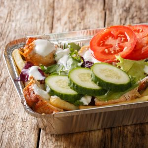 Takeaway Dutch kapsalon from french fries, chicken, fresh salad, cheese and sauce in a close-up foil tray. horizontal